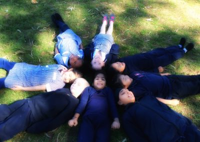 Photo of a group of children laying down on the grass