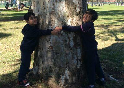 Photo of two children hugging a tree